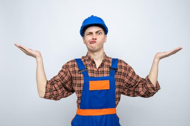 Verwarde spreidende handen jonge mannelijke bouwer die uniform draagt