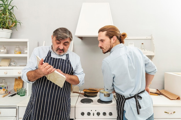 Verwarde vader en zoon die in een kookboek kijken