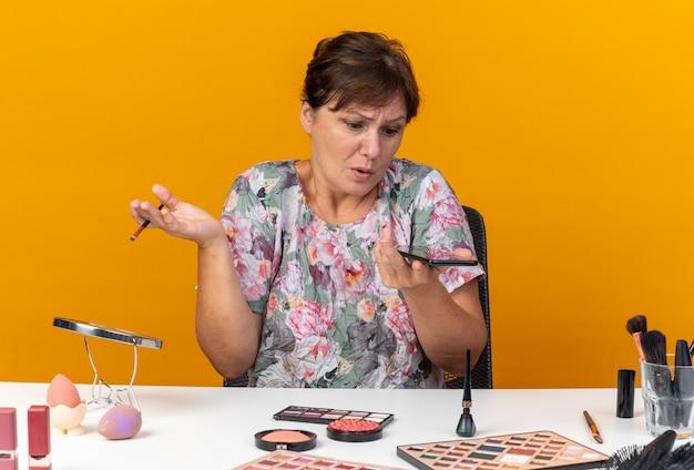 Verwarde volwassen blanke vrouw die aan tafel zit met make-uptools die make-upborstel vasthoudt en naar telefoon kijkt die op een oranje muur met kopieerruimte is geïsoleerd