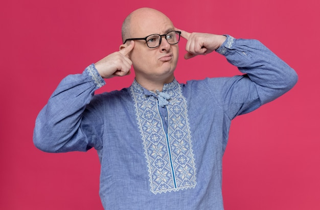 Verwarde volwassen man in blauw shirt met een bril die vingers op zijn slapen legt en naar de zijkant kijkt