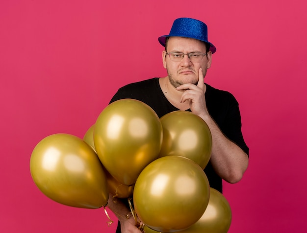 Verwarde volwassen slavische man met optische bril met blauwe feestmuts legt hand op kin en houdt heliumballonnen vast