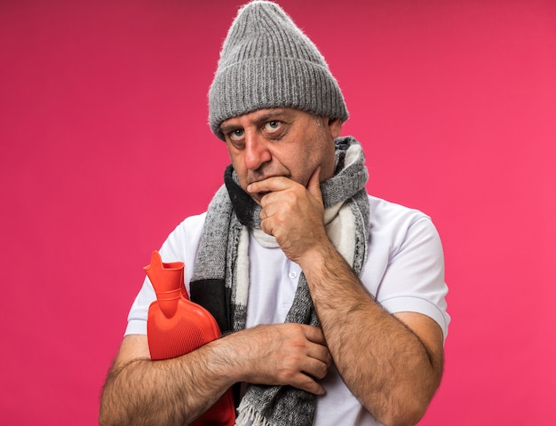Verwarde volwassen zieke blanke man met sjaal om de nek met winterhoed legt hand op kin en houdt warmwaterkruik kijkt naar kant geïsoleerd op roze muur met kopie ruimte