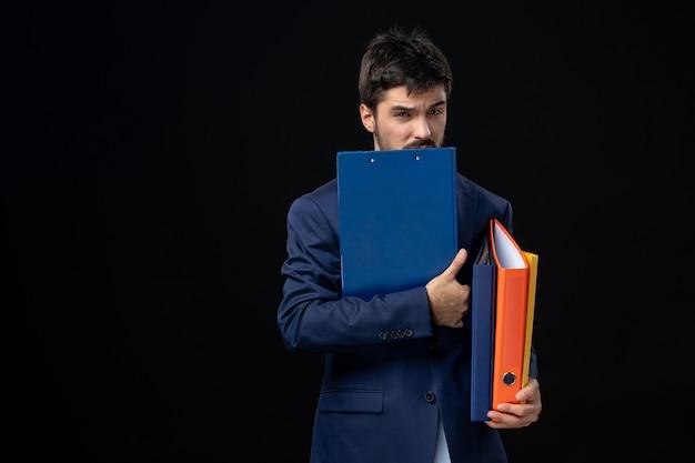 Verwarde volwassene in pak met verschillende documenten en poseren op geïsoleerde donkere muur