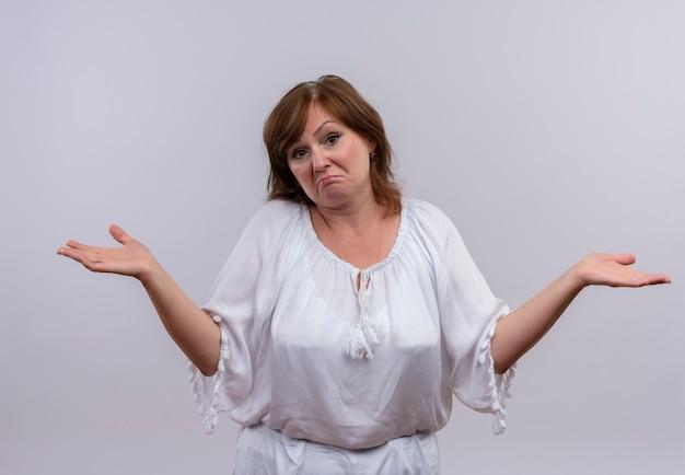 Verwarde vrouw die op middelbare leeftijd lege handen op geïsoleerde witte muur toont