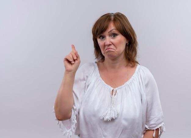 Verwarde vrouw die op middelbare leeftijd met vinger omhoog op geïsoleerde witte muur richt
