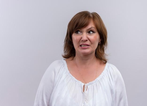 Verwarde vrouw die op middelbare leeftijd naar linkerkant op geïsoleerde witte muur kijkt