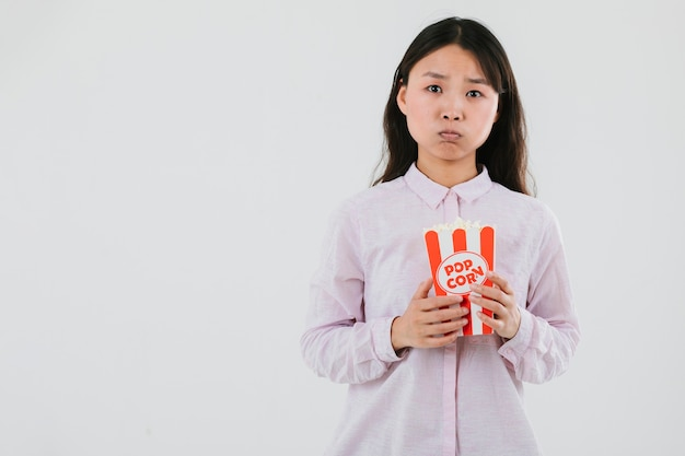 Verwarde vrouw die popcorn eet
