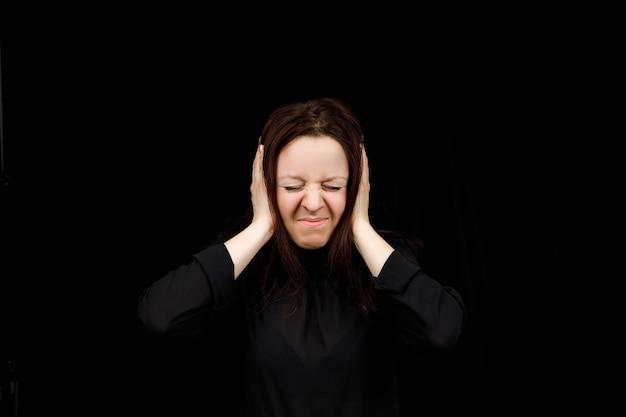 Verwarde vrouw hand in hand op hoofd over zwarte studio achtergrond. portret van een jong meisje dat haar oren sluit, hoor geen kwaad, doofheid concept, kopieer ruimte.