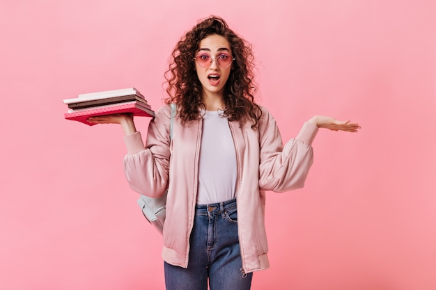 Verwarde vrouw in roze outfit met boeken en poseren op geïsoleerde achtergrond
