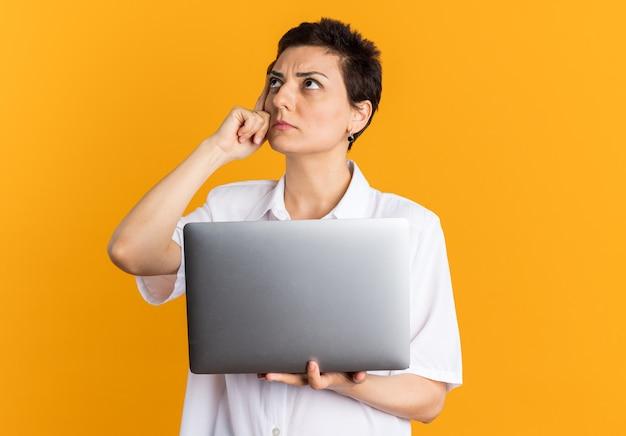 Verwarde vrouw van middelbare leeftijd die een laptop vasthoudt die opkijkt en een denkgebaar doet