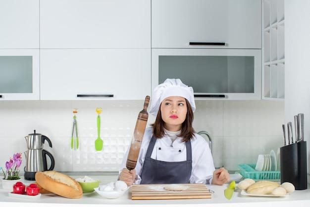 Verwarde vrouwelijke commischef in uniform die achter tafel staat en gebak bereidt in de witte keuken