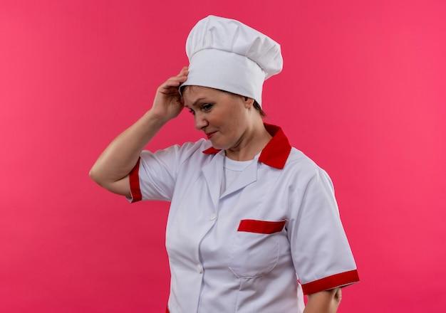 Verwarde vrouwelijke kok van middelbare leeftijd in eenvormige chef-kok die hand op voorhoofd op geïsoleerde roze muur zet