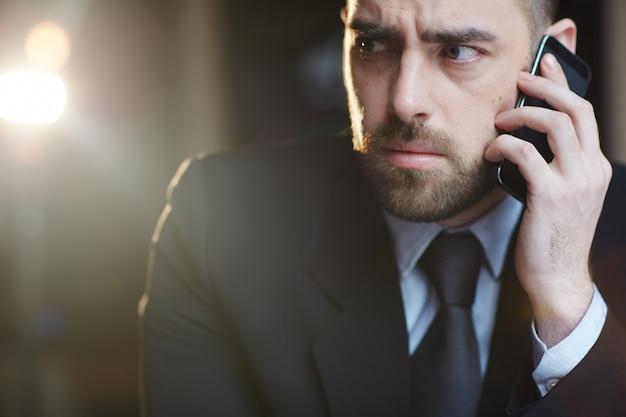 Verwarde zakenman die door smartphone spreekt