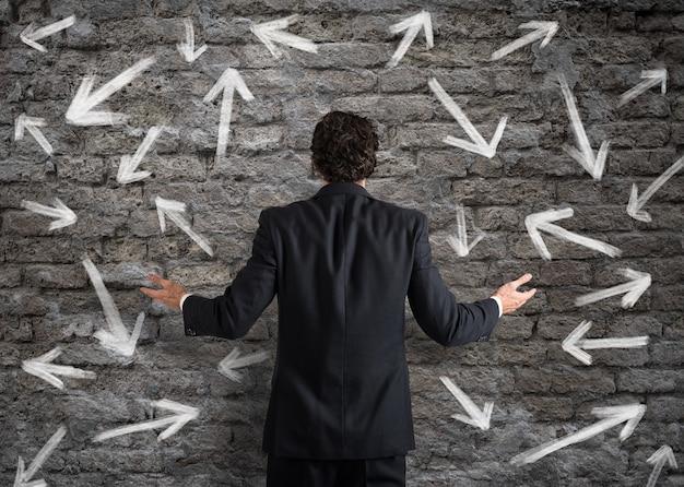 Verwarde zakenman die een muur met richtingspijlen kijkt