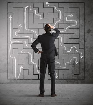 Verwarde zakenman zoekt een oplossing voor het labyrint dat aan de muur is getekend