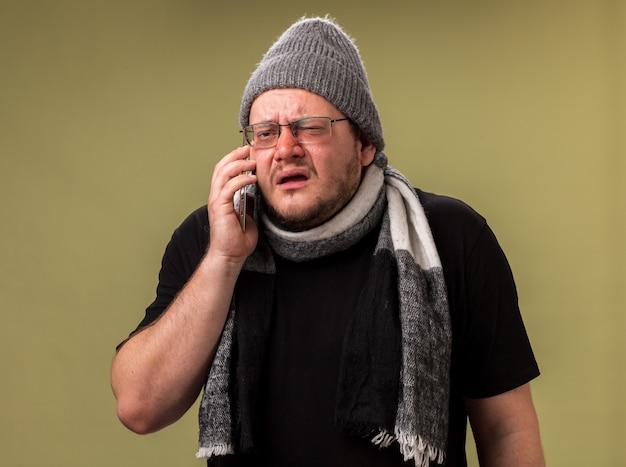 Verwarde zieke man van middelbare leeftijd met wintermuts en sjaal spreekt aan de telefoon