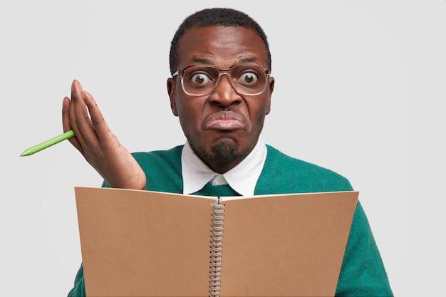 Verwarde zwarte jongeman heeft een aarzelende uitdrukking, weet niet wat hij moet schrijven, houdt leerboek en pen vast, bereidt verhaal voor over zijn vakantie