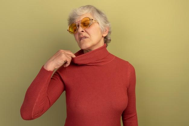 Verwarmde oude vrouw met een rode coltrui en een zonnebril die de kraag van haar trui trekt met gesloten ogen geïsoleerd op een olijfgroene muur met kopieerruimte