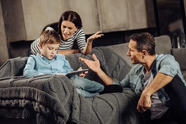 Verwarmde ruzie. bezorgde, van streek gemaakte ouders die tegen hun zoon schreeuwden, hem ervan te overtuigen te stoppen met bingespelen aan de telefoon, terwijl de jongen geen aandacht aan hen schonk