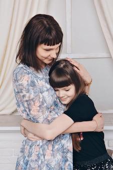 Verwarmend en ontspannend bij de open haard. moeder en dochter knuffelen. concept van familie, moederschap, interieur, huis, jeugd, moederdag, kinderdag