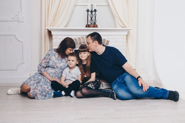 Verwarmend en ontspannend bij de open haard. moeder, vader en dochter, zoon knuffelen. concept van familie, moederschap, interieur, huis, jeugd, moederdag, kinderdag
