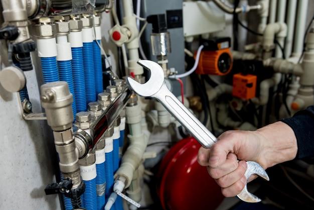 Verwarmingsingenieur die modern verwarmingssysteem installeert in stookruimte. automatische controle-eenheid.