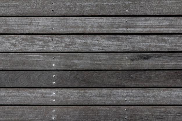Verweerde houten plankenvloer textuur. houten bestrating achtergrond. het abstracte patroon van het huisdek