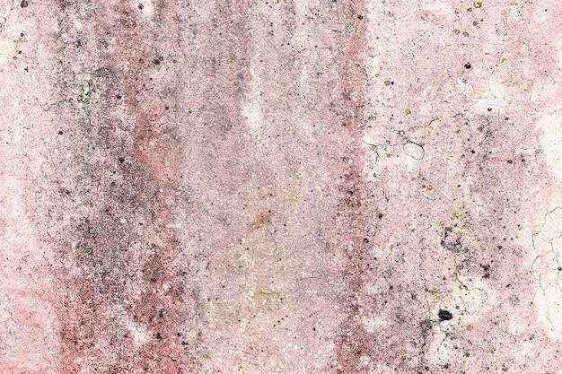 Verweerde muur met vocht en roze en witte verfresten