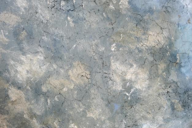 Verweerde oude grijze gebarsten achtergrond met ruw oppervlak.