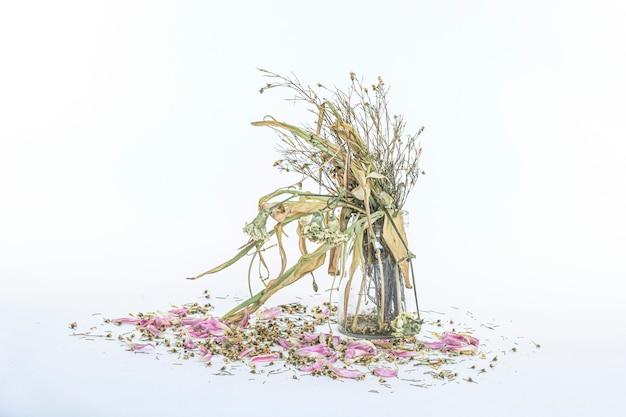 Verwelkt bloemenboeket in een heldere glazen vaas, vintage gefilterd