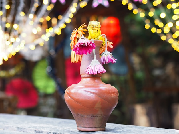 Verwelkt gerbera-bloem in bruine vaas op houten lijst