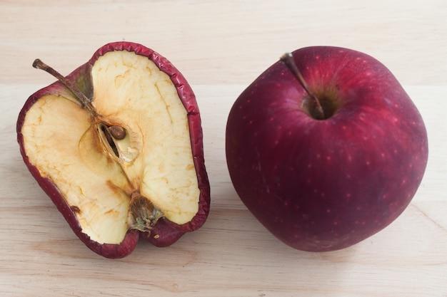 Verwend een slechte rode appel op houten achtergrond gezonde en rote appels