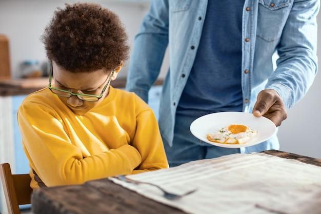 Verwend kind. pre-tienerjongen met krullend haar die geen vriendenei wil hebben als ontbijt en zijn gezicht van het bord afkeert