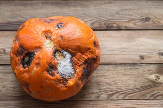 Verwende oranje pompoen met schimmel op een houten achtergrond.