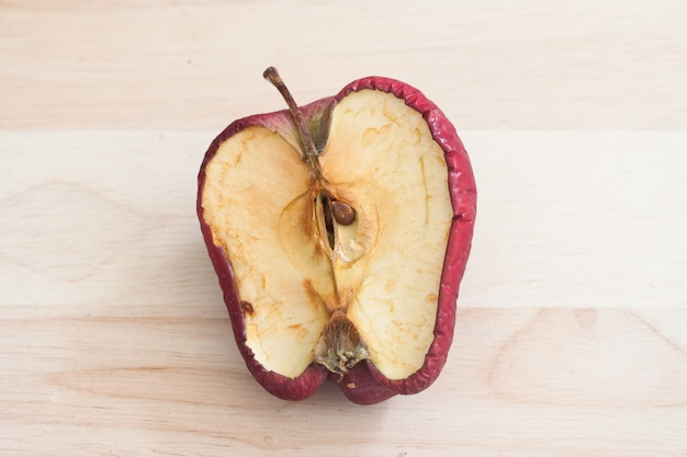 Verwende slechte rode appel op houten achtergrond