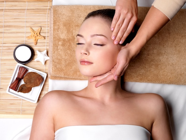 Verwennerij en massage voor mooi gezicht van jonge vrouw in spa salon