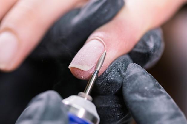Verwerk manicure close-up. voorbereiding voor hardwaremanicure. schoonheidsspecialiste in rubberen handschoenen snijdt de