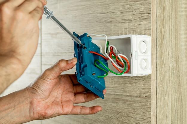 Verwijder de elektrische stekker uit het stopcontact op de houten muur om de spanning te controleren met een schroevendraaier.