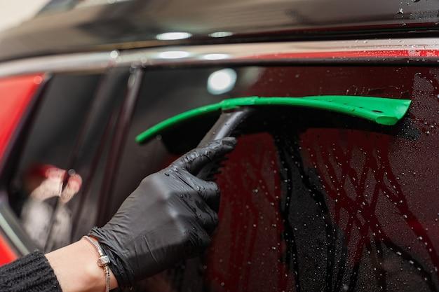 Verwijderen van restwater van het glas met een rubberen schraper na het wassen van de auto. carwash. zelfbedieningscomplex. autowassen onder hoge druk.