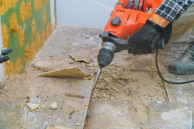 Verwijdering van oude vloer tijdens een renovatie van woningen van sloophamer, fragmenten van keramische tegels