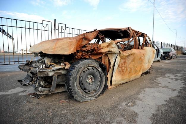 Verwoeste en brandende auto op de weg