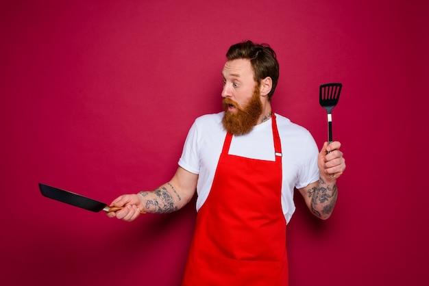 Verwonderde chef-kok met baard en rode schort is klaar om te koken