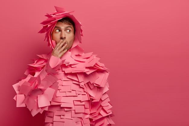 Verwonderde jongeman bedekt mond, kijkt met angstige uitdrukking opzij, covers met veel plakbriefjes, draagt creatief papier gemaakt kostuum, geïsoleerd op roze muur, lege ruimte aan de rechterkant