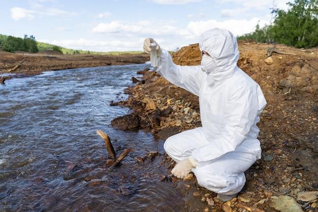 Verzamelen watermonsters voor analyse van de verontreiniging dicht bij een industrieel complex