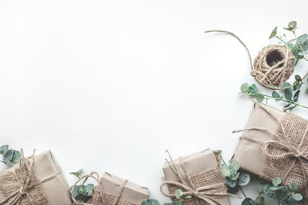 Verzameling geschenkdozen verpakt in minimale stijl van kraftpapier met bladeren
