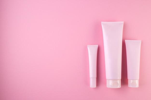 Verzameling van drie cosmetische buizen op pastelroze