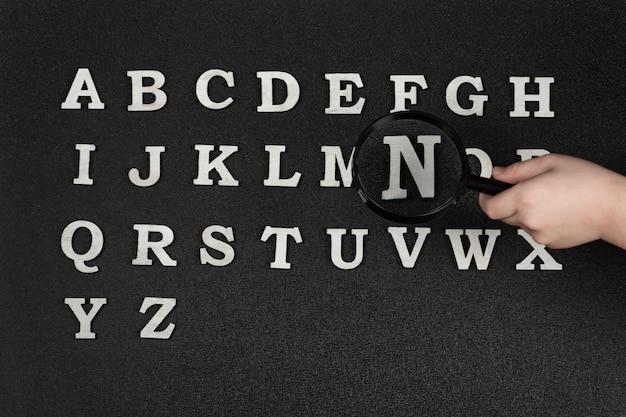 Verzameling van engelse letters alfabetische volgorde van a tot z. hand met vergrootglas over letters.