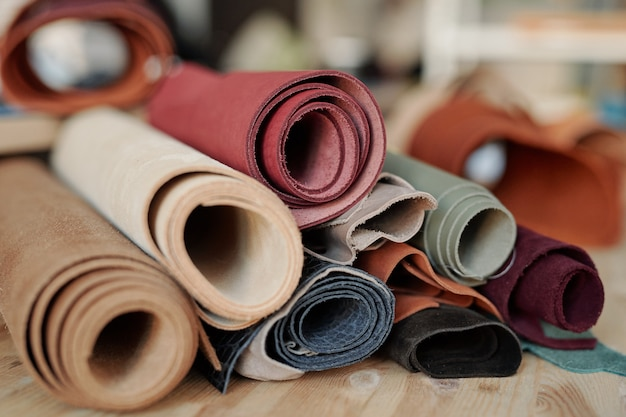 Verzameling van gerold suède en leer van verschillende kleuren liggend op houten tafel in werkplaats van leerbewerker