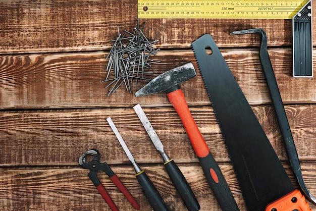 Verzameling van houtbewerkingsgereedschap op een houten tafel en kopie ruimte: timmerwerk, vakmanschap en handgemaakte concept, plat leggen. zaag, hamer, beitel, spijkers, liniaal.
