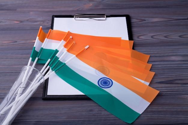 Verzameling van indiase vlaggen op het klembord met blanco papier